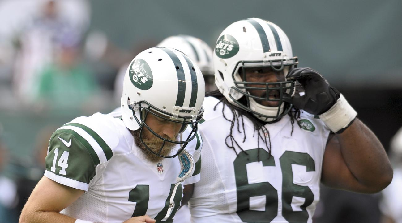 New York Jets quarterback Ryan Fitzpatrick (14) jogs off the field with guard Willie Colon (66) after failing to convert on third down against the Philadelphia Eagles during the second quarter of an NFL football game, Sunday, Sept. 27, 2015, in East Ruthe