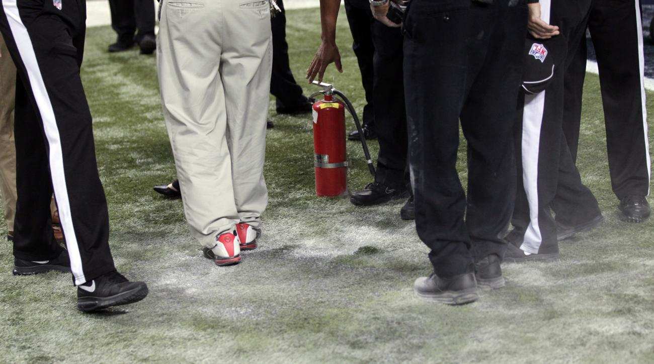 Workers and officials stand over a section of charred turf burned during pyrotechnics before an NFL football game between the St. Louis Rams and the Pittsburgh Steelers, Sunday, Sept. 27, 2015, in St. Louis. (AP Photo/Tom Gannam)