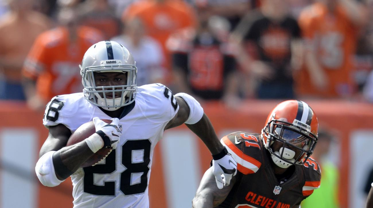 Oakland Raiders running back Latavius Murray (28) runs the ball ahead of Cleveland Browns strong safety Donte Whitner (31) during the second half of an NFL football game, Sunday, Sept. 27, 2015, in Cleveland. (AP Photo/David Richard)