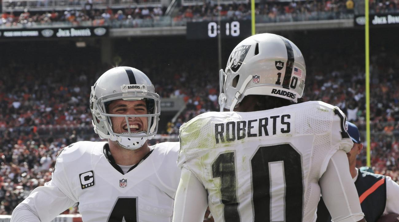 Oakland Raiders quarterback Derek Carr (4) smiles after wide receiver Seth Roberts, right, scored on a 13-yard reception during the first half of an NFL football game against the Cleveland Browns, Sunday, Sept. 27, 2015, in Cleveland. (AP Photo/Aaron Jose