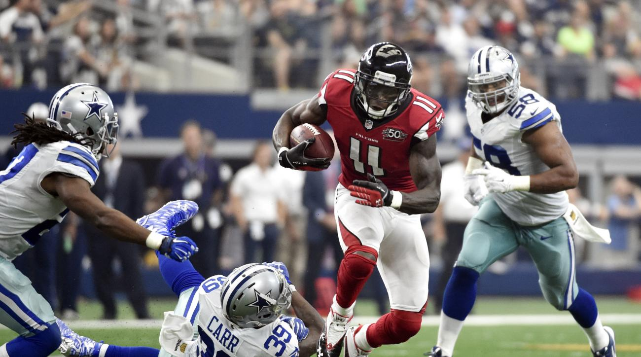 Atlanta Falcons wide receiver Julio Jones (11) breaks a tackle attempt by Dallas Cowboys' Brandon Carr (39) as J.J. Wilcox, left, and Jack Crawford (58) assist on the play in the second half of an NFL football game on Sunday, Sept. 27, 2015, in Arlington,