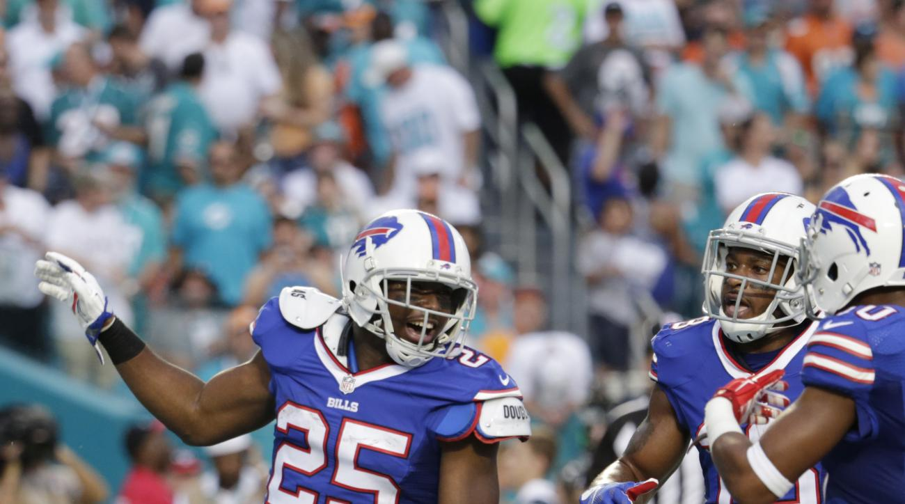 Buffalo Bills running back LeSean McCoy (25) celebrates his touchdown during the first half of an NFL football game against the Miami Dolphins, Sunday, Sept. 27, 2015 in Miami Gardens, Fla. To the right is Buffalo Bills wide receiver Percy Harvin (18) and