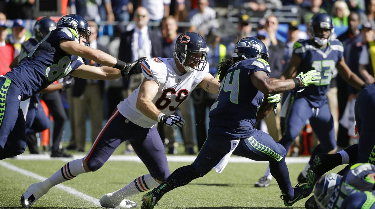 Seattle Seahawks running back Marshawn Lynch (24) runs the ball as Chicago Bears outside linebacker Jared Allen (69) reaches for a tackle attempt while being blocked by Seahawks' tight end Cooper Helfet, left, in the first half of an NFL football game, Su