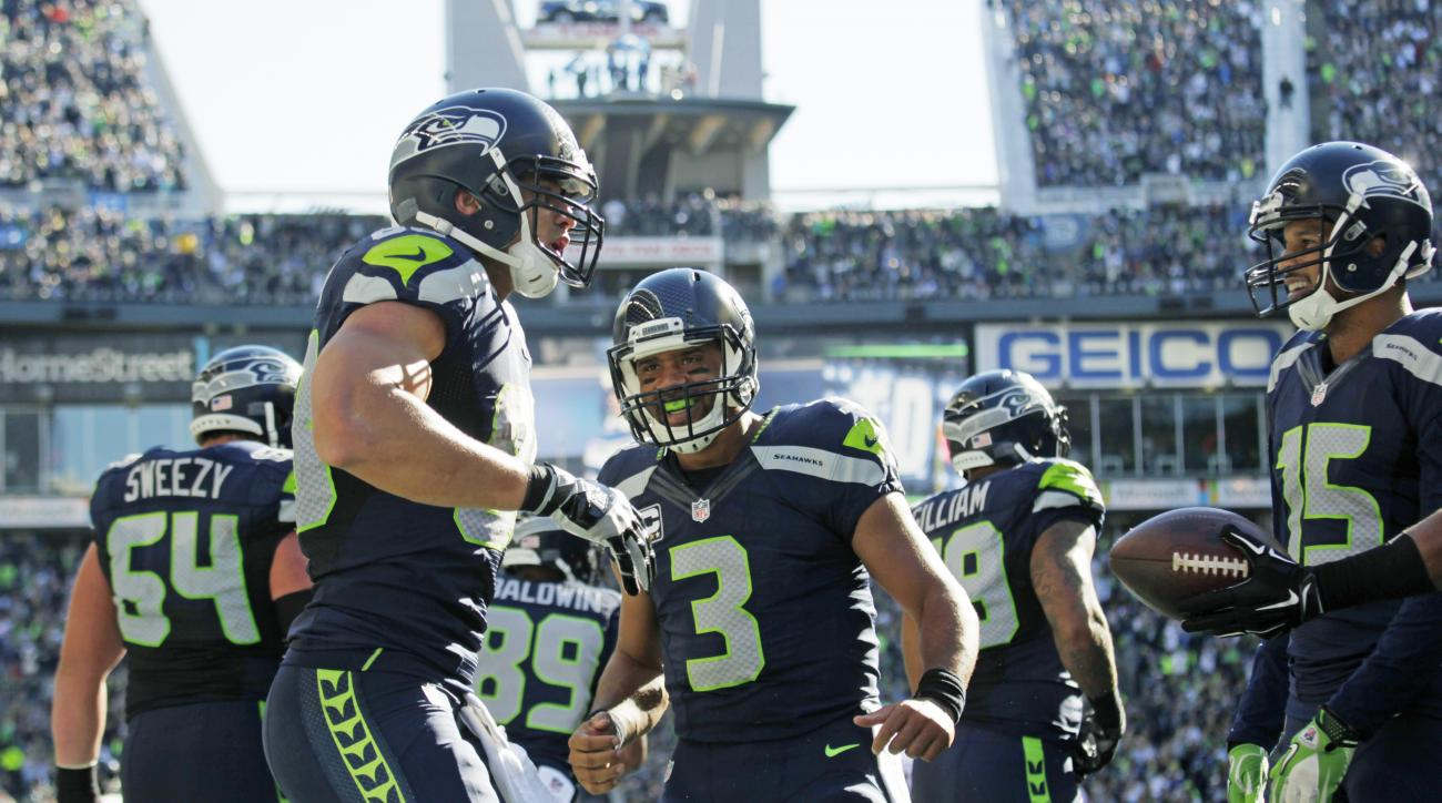 Seattle Seahawks quarterback Russell Wilson (3) celebrates with tight end Jimmy Graham, left, after Graham caught a pass from Wilson for a touchdown against the Chicago Bears in the second half of an NFL football game, Sunday, Sept. 27, 2015, in Seattle.
