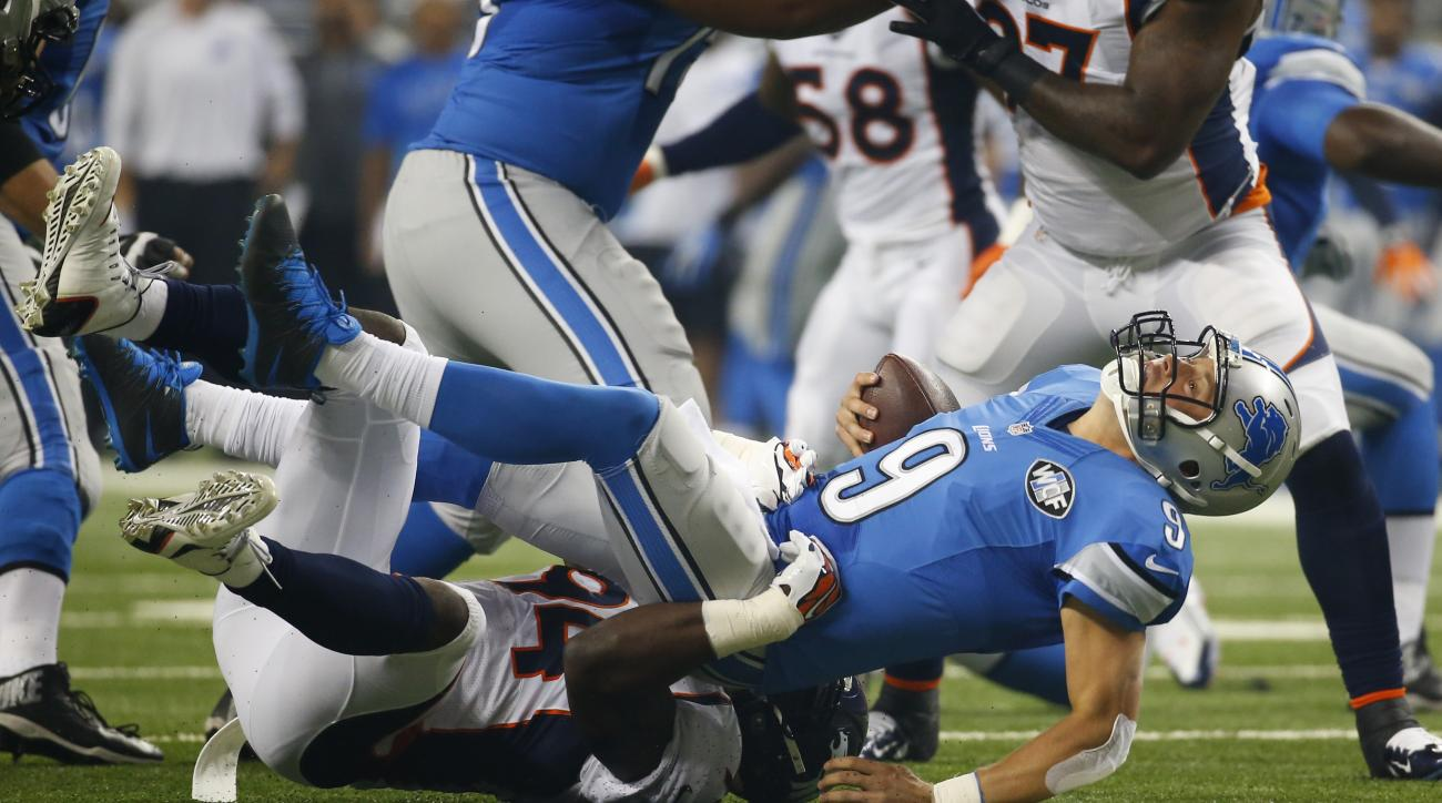 Detroit Lions quarterback Matthew Stafford (9) is sacked by Denver Broncos outside linebacker DeMarcus Ware during the first half of an NFL football game, Sunday, Sept. 27, 2015, in Detroit. (AP Photo/Paul Sancya)