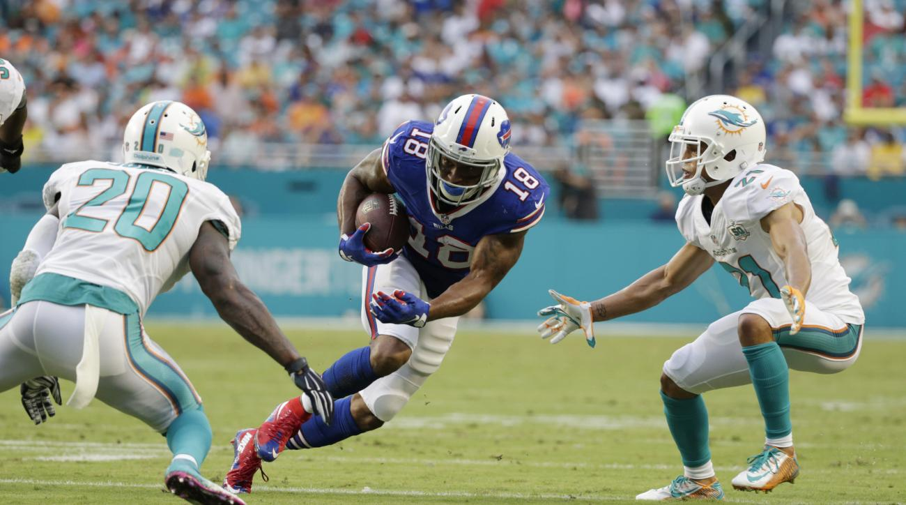 Buffalo Bills wide receiver Percy Harvin (18) runs the ball between Miami Dolphins strong safety Reshad Jones (20) and cornerback Brent Grimes (21) during the first half of an NFL football game, Sunday, Sept. 27, 2015, in Miami Gardens, Fla. Miko Grimes,