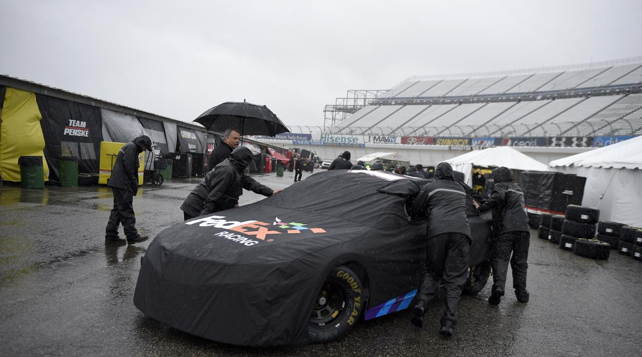 Crew members push the race car of Denny Hamlin in the garage area for the NASCAR Sprint Cup series auto race, Friday, Oct. 2, 2015, at Dover International Speedway in Dover, Del. (AP Photo/Nick Wass)