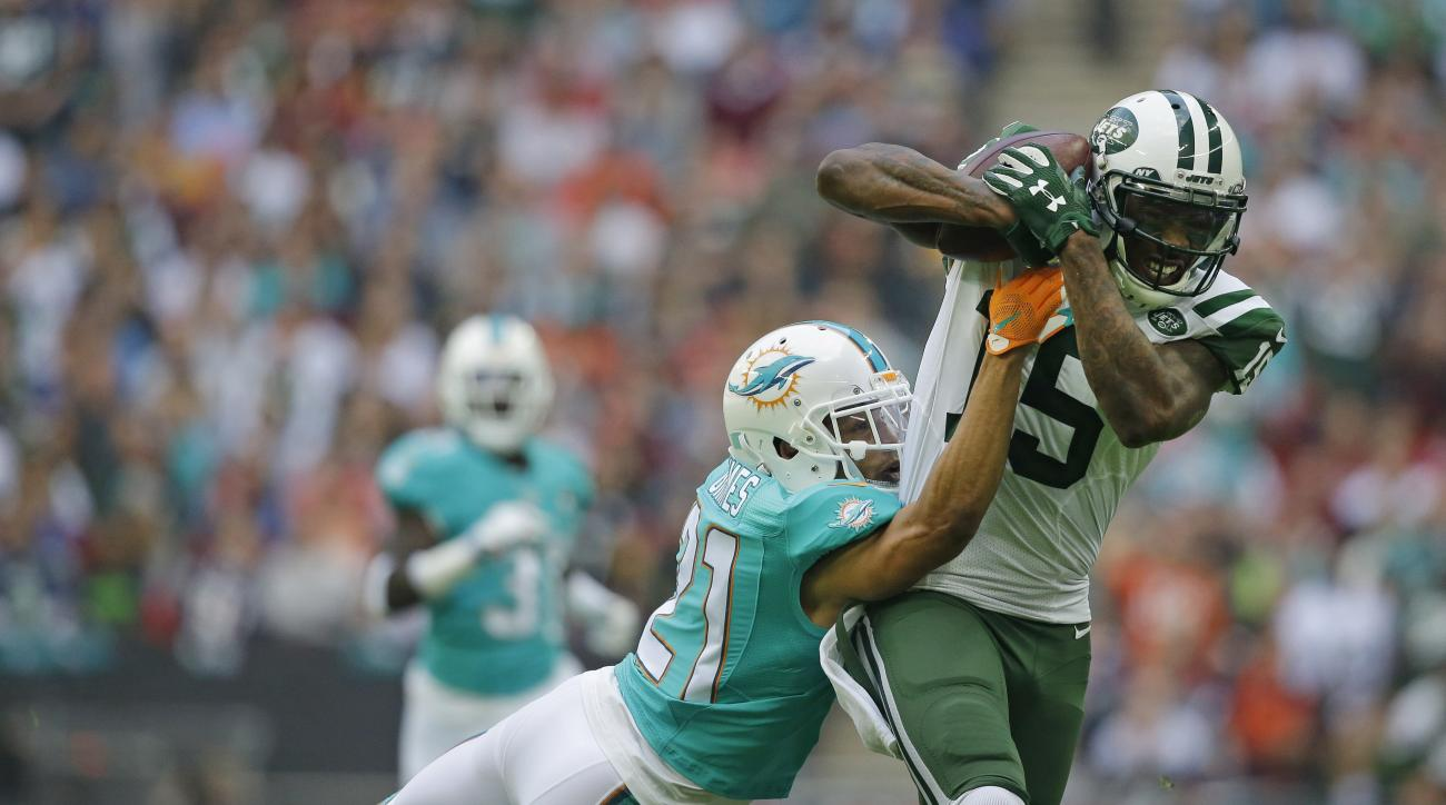 New York Jets' Brandon Marshall, right, catches the ball despite the challenge of Miami Dolphins' Brent Grimes during the NFL football game between the New York Jets and the Miami Dolphins and at Wembley stadium in London, Sunday, Oct. 4, 2015. (AP Photo/
