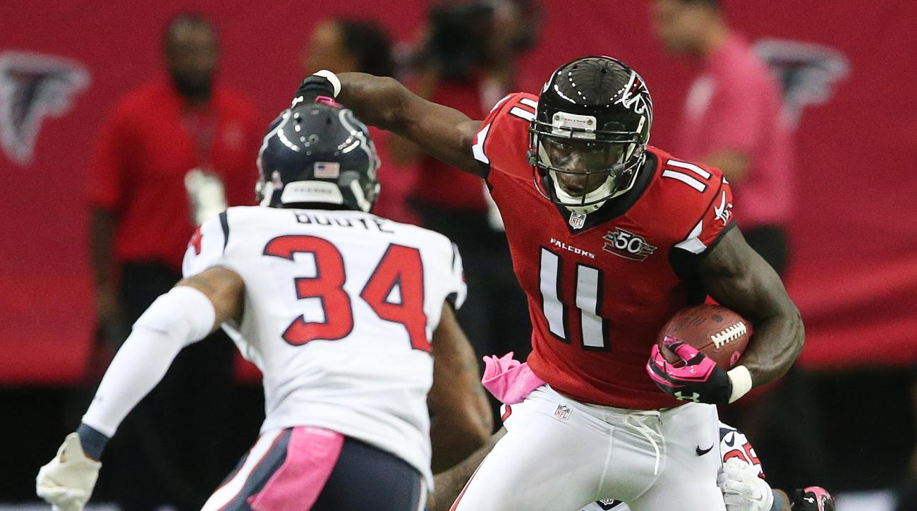 Atlanta Falcons wide receiver Julio Jones (11) is tackled by Houston Texans cornerback Kareem Jackson, rear, as Houston Texans cornerback A.J. Bouye (34) looks on during the first half of an NFL football game, Sunday, Oct. 4, 2015, in Atlanta. (AP Photo/J