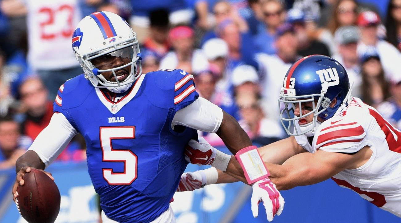 Buffalo Bills quarterback Tyrod Taylor, left, avoids a sack by New York Giants safety Craig Dahl during the second half of an NFL football game, Sunday, Oct. 4, 2015, in Orchard Park, N.Y. (AP Photo/Gary Wiepert)