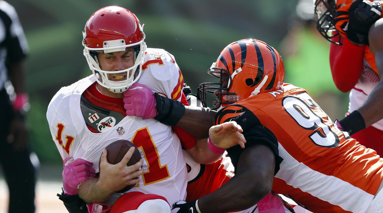 Kansas City Chiefs quarterback Alex Smith (11) is sacked by Cincinnati Bengals defensive end Carlos Dunlap, behind, with assistance from defensive tackle Geno Atkins (97) in the second half of an NFL football game, Sunday, Oct. 4, 2015, in Cincinnati. (AP