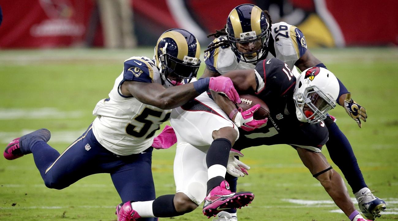 Arizona Cardinals running back David Johnson (31) his hit by St. Louis Rams outside linebacker Alec Ogletree (52) and safety Mark Barron (26) during the first half of an NFL football game, Sunday, Oct. 4, 2015, in Glendale, Ariz. (AP Photo/Ross D. Frankli