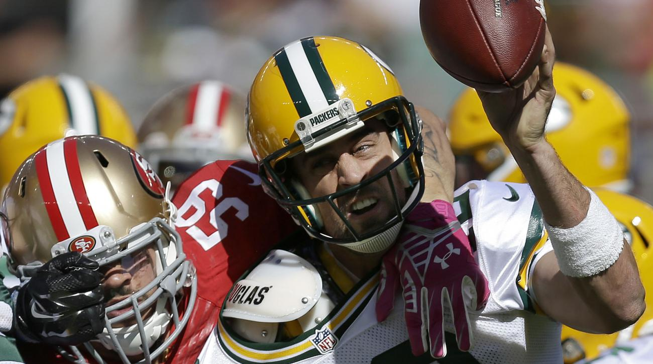 Green Bay Packers quarterback Aaron Rodgers (12) gets rid of the ball as he is pressured by San Francisco 49ers linebacker Aaron Lynch (59) during the first half of an NFL football game in Santa Clara, Calif., Sunday, Oct. 4, 2015. (AP Photo/Ben Margot)