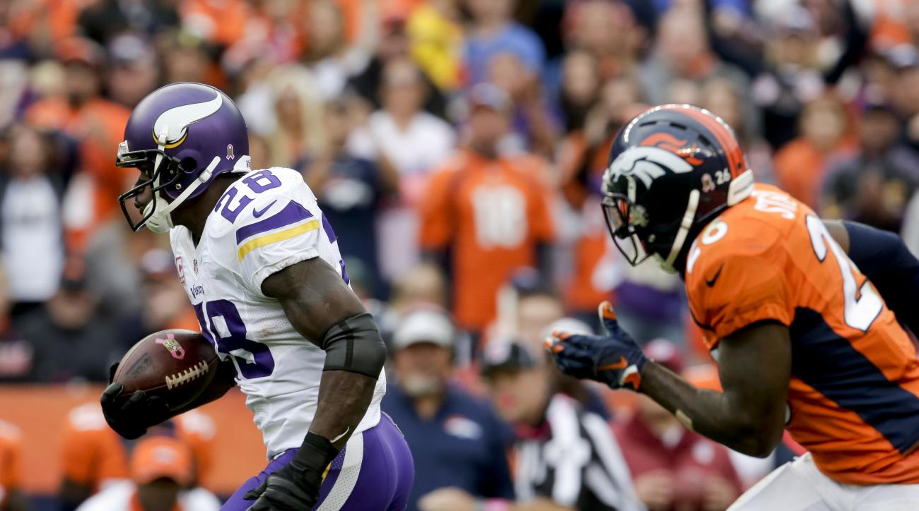 Minnesota Vikings running back Adrian Peterson scores ahead of Denver Broncos free safety Darian Stewart during the second half of an NFL football game Sunday, Oct. 4, 2015, in Denver. (AP Photo/Joe Mahoney)