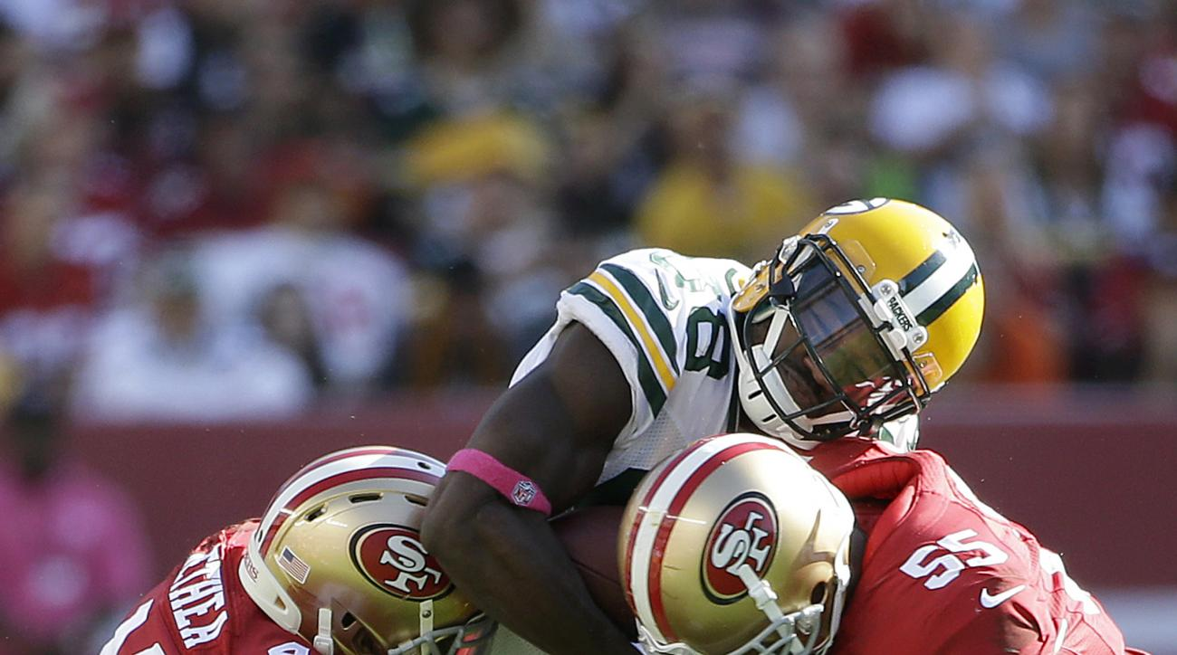 Green Bay Packers wide receiver Ty Montgomery, center, is tackled by San Francisco 49ers strong safety Antoine Bethea (41) and linebacker Ahmad Brooks (55) during the second half of an NFL football game in Santa Clara, Calif., Sunday, Oct. 4, 2015. (AP Ph