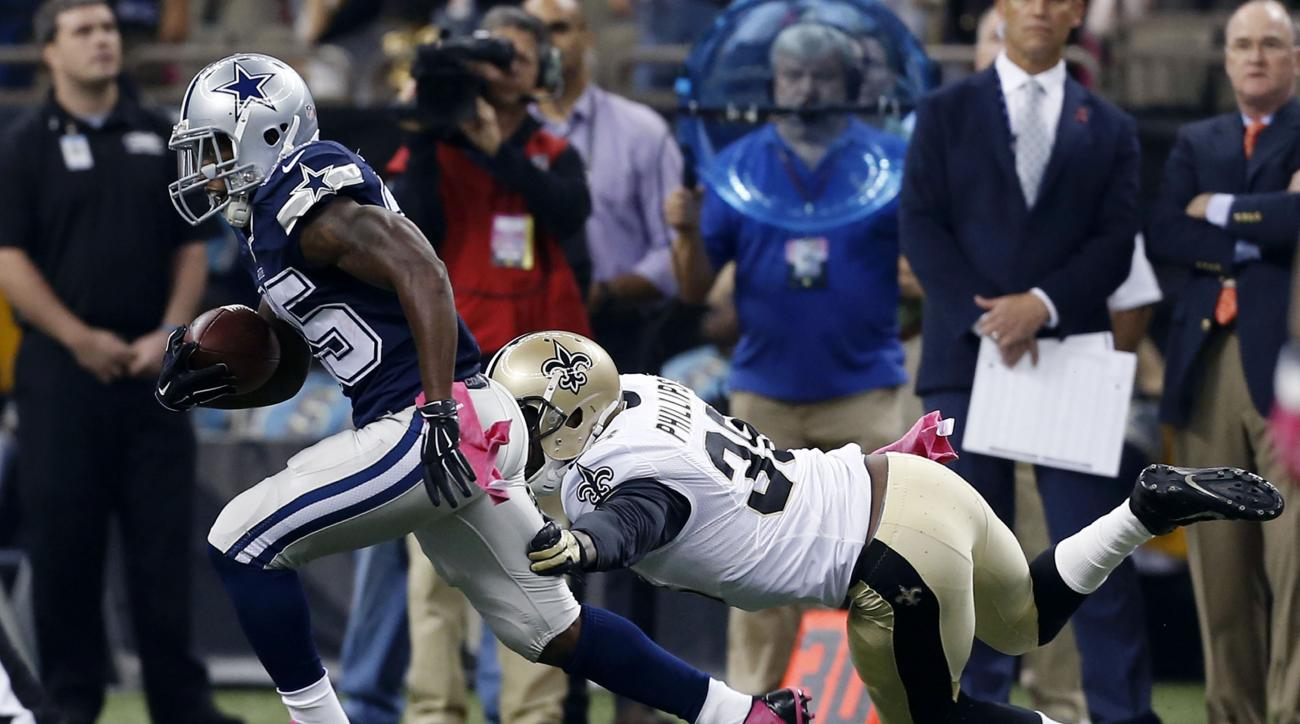 Dallas Cowboys running back Lance Dunbar (25) carries as New Orleans Saints free safety Kenny Phillips (38) pursues in the first half of an NFL football game in New Orleans, Sunday, Oct. 4, 2015. (AP Photo/Jonathan Bachman)