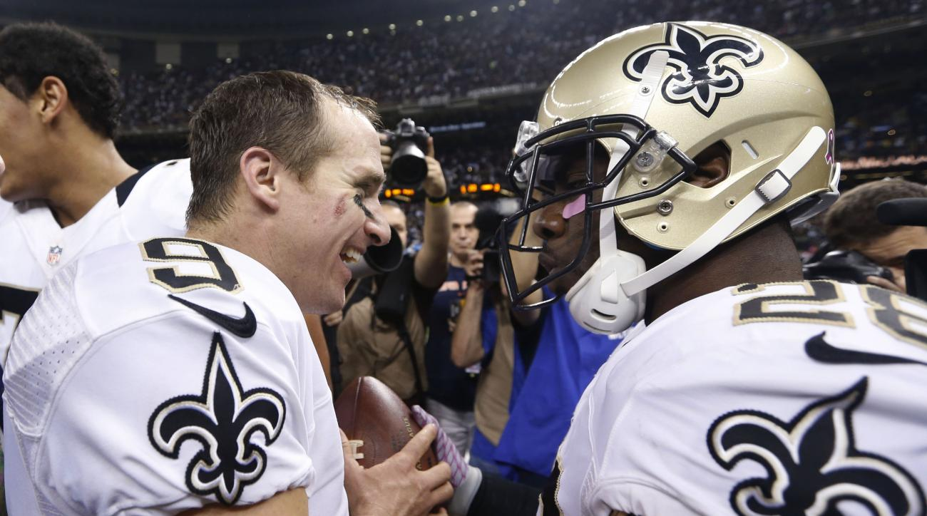 New Orleans Saints quarterback Drew Brees (9) and running back C.J. Spiller (28) greet each other after their overtime NFL football game win over Dallas Cowboys in New Orleans, Sunday, Oct. 4, 2015. The Saints won 26-20. (AP Photo/Jonathan Bachman)