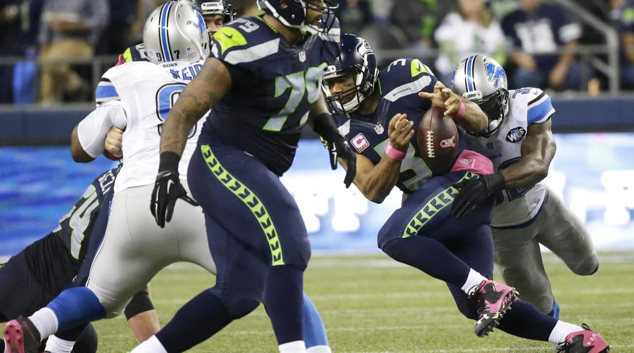 Seattle Seahawks quarterback Russell Wilson fumbles as he his tackled by Detroit Lions strong safety James Ihedigbo, right, in the second half of an NFL football game, Monday, Oct. 5, 2015, in Seattle. Lions' Caraun Reid recovered the fumble and ran for a