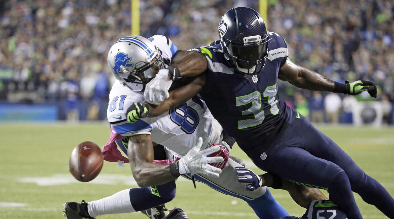 Seattle Seahawks strong safety Kam Chancellor (31) knocks the ball loose from Detroit Lions wide receiver Calvin Johnson (81) in the second half of an NFL football game, Monday, Oct. 5, 2015, in Seattle. The fumble went out of bounds in the end zone and w