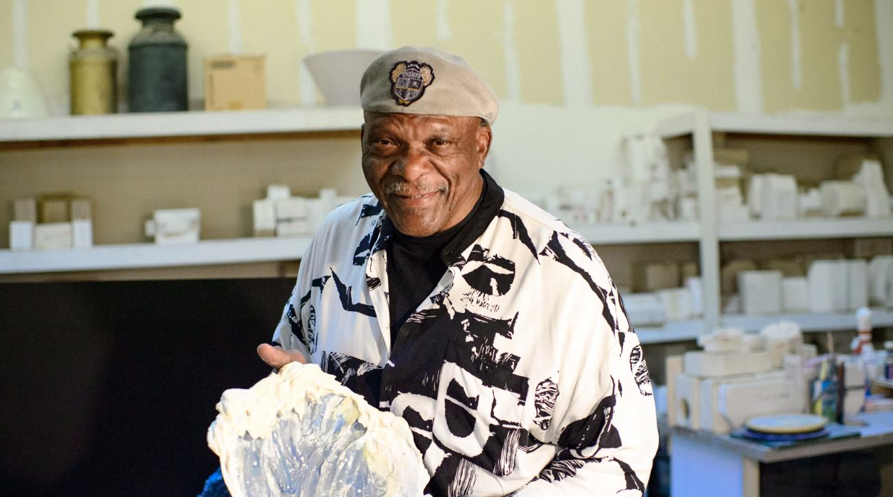 In this Monday, Oct. 5, 2015, photo, former Minnesota Viking football player Carl Eller poses with some of his ceramic artwork, patterned after Minnesota Lakes, that will be part of a display at the new Vikings Stadium. (Glen Stubbe/Star Tribune via AP)