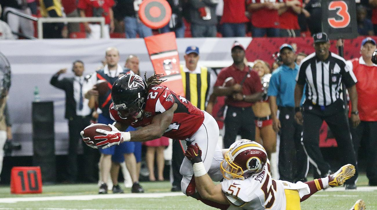 Atlanta Falcons running back Devonta Freeman (24) reaches for the goal line as Washington Redskins inside linebacker Will Compton (51) during the second half of an NFL football game, Sunday, Oct. 11, 2015, in Atlanta. The play was ruled a touchdown then r