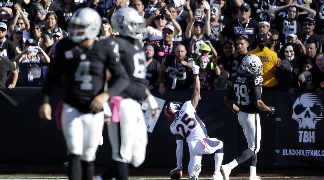 Denver Broncos cornerback Chris Harris (25) celebrates after returning an interception from Oakland Raiders quarterback Derek Carr (4) for a 74-yard touchdown during the second half of an NFL football game in Oakland, Calif., Sunday, Oct. 11, 2015. (AP Ph