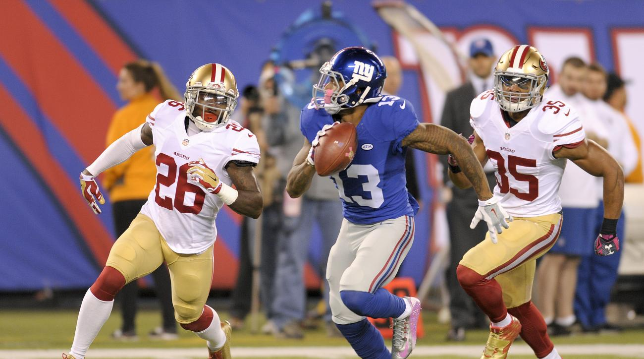 New York Giants wide receiver Odell Beckham (13) takes the ball up field after making a catch against San Francisco 49ers cornerback Tramaine Brock (26) and free safety Eric Reid (35) during the first quarter of an NFL football game, Sunday, Oct. 11, 2015