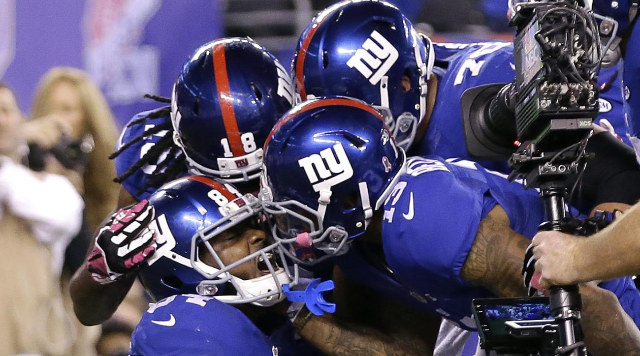 New York Giants tight end Larry Donnell (84) is congratulated by teammates after scoring the game-winning touchdown against the San Francisco 49ers during the fourth quarter of an NFL football game, Sunday, Oct. 11, 2015, in East Rutherford, N.J. The Gian