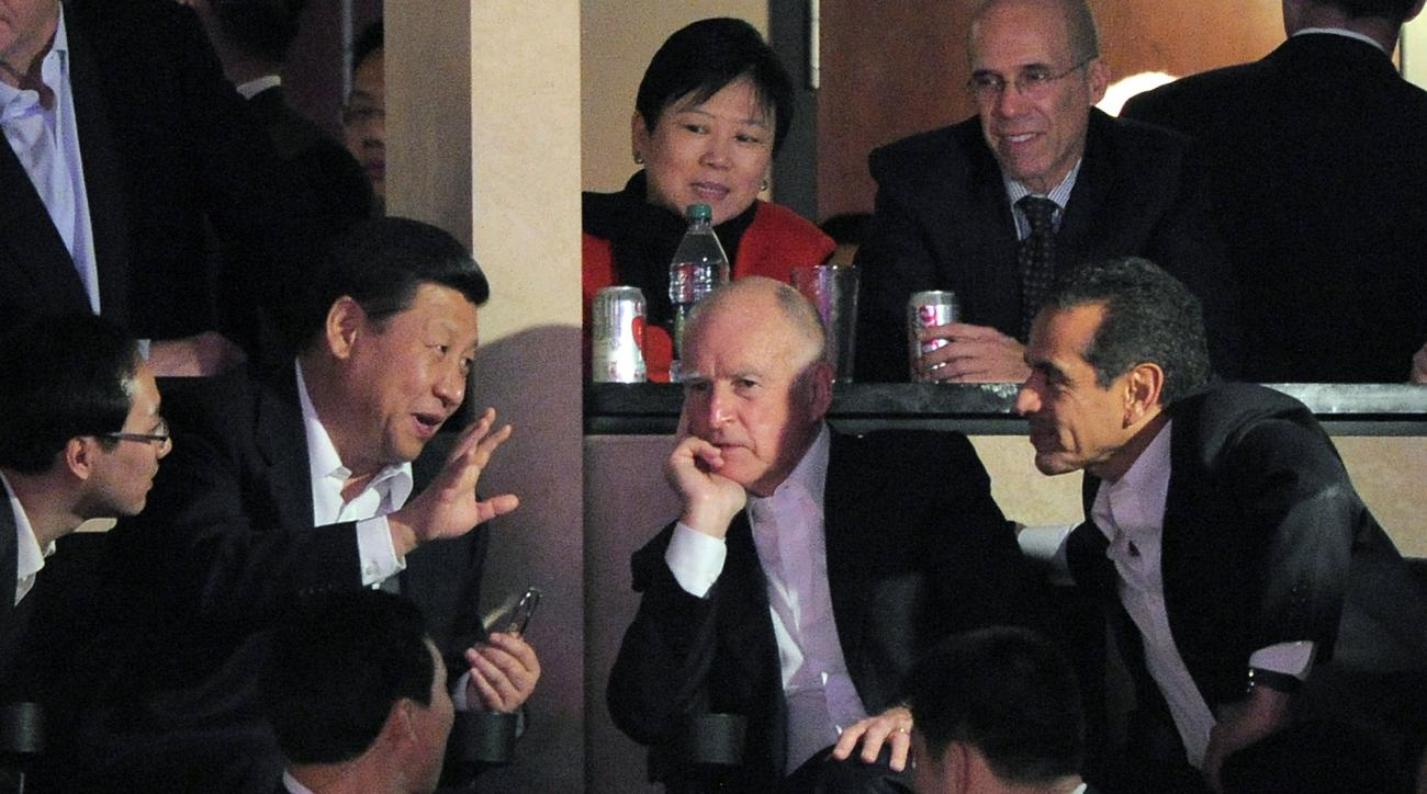 Chinese Vice President Xi Jinping, left, sits with Calif. Gov. Jerry Brown, center, and Los Angeles Mayor Antonio Villaraigosa as they watch the Los Angeles Lakers play the Phoenix Suns, Friday, Feb. 17, 2012, in Los Angeles.  Xi is set to lead China for