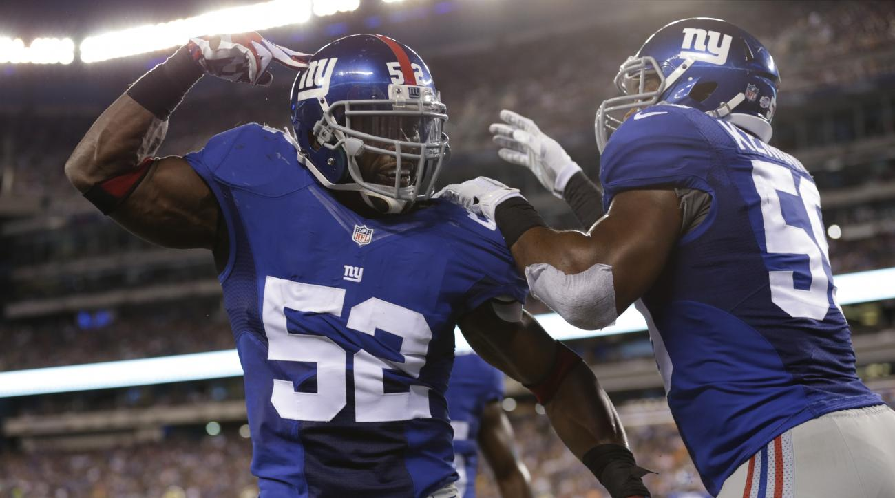 New York Giants middle linebacker Jon Beason (52) celebrate with teammate Devon Kennard (59) after breaking up a pass to Jacksonville Jaguars' Denard Robinson during the first half of a preseason NFL football game Saturday, Aug. 22, 2015, in East Rutherfo