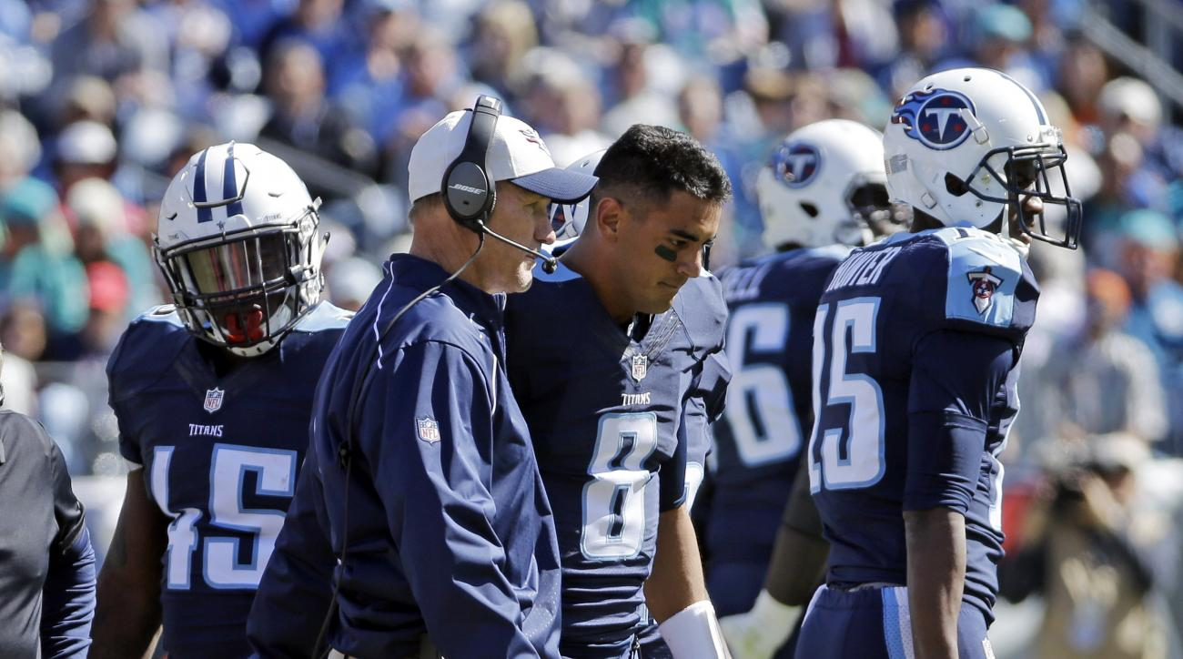 Tennessee Titans quarterback Marcus Mariota (8) walks off the field with head coach Ken Whisenhunt after Mariota was injured in the first half of an NFL football game against the Miami Dolphins Sunday, Oct. 18, 2015, in Nashville, Tenn. (AP Photo/James Ke