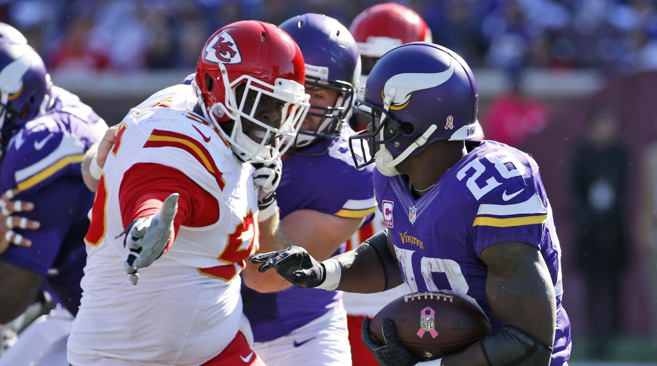 Kansas City Chiefs outside linebacker Tamba Hali (91) reaches for Minnesota Vikings running back Adrian Peterson (28) during the first half of an NFL football game, Sunday, Oct. 18, 2015, in Minneapolis. (AP Photo/Ann Heisenfelt)