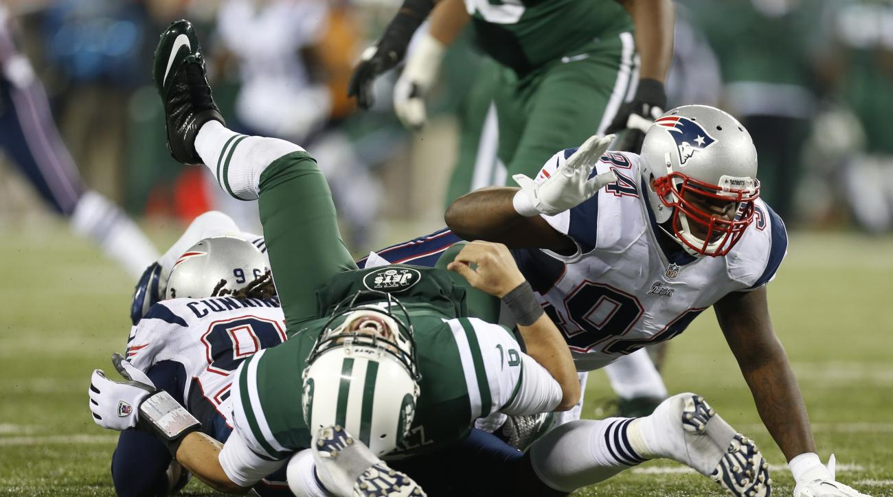 FILE - In this Nov. 22, 2012, file photo, New York Jets quarterback Mark Sanchez is hit by New England Patriots defensive end Jermaine Cunningham (96) and Justin Francis (94) during the second half of an NFL football game in East Rutherford, N.J. Earlier