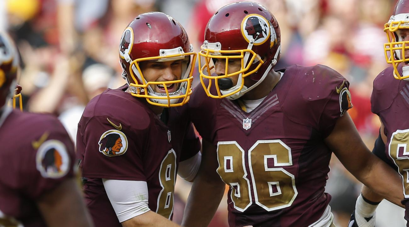 Washington Redskins quarterback Kirk Cousins (8) congratulates tight end Jordan Reed (86) after Reed scored the tying touchdown during the second half of an NFL football game in Landover, Md., Sunday, Oct. 25, 2015. The Washington Redskins defeated the Ta