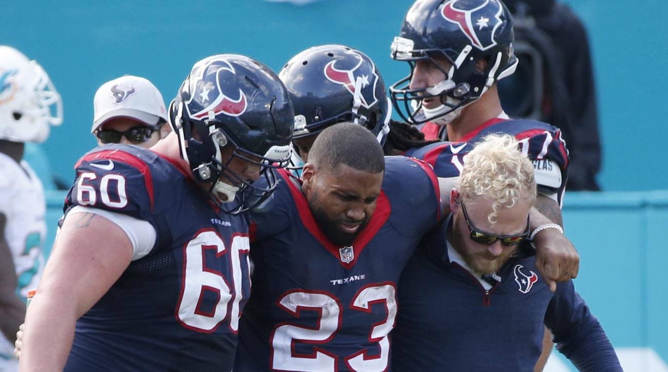 Houston Texans running back Arian Foster (23) struggles to walk as he is helped off the field by center Ben Jones (60) and an unidentified team member, during the second half of an NFL football game against the Miami Dolphins, Sunday, Oct. 25, 2015 in Mia