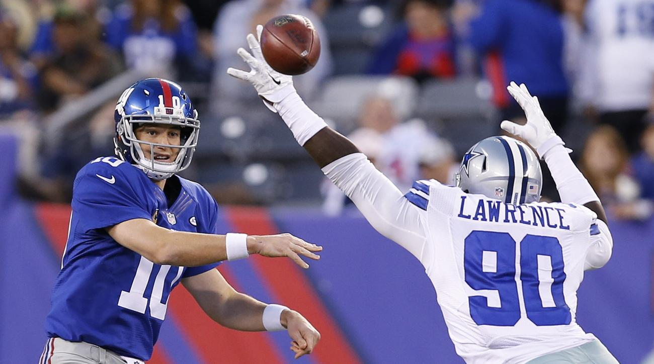 New York Giants quarterback Eli Manning (10) throws a pass as Dallas Cowboys' Demarcus Lawrence (90) rushes him during the first half of an NFL football game Sunday, Oct. 25, 2015, in East Rutherford, N.J. (AP Photo/Kathy Willens)