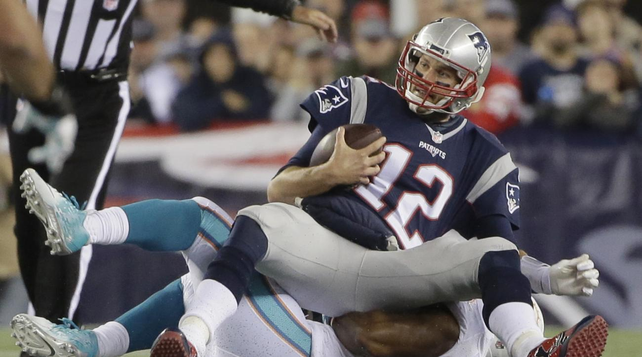 Miami Dolphins defensive end Cameron Wake (91) sacks New England Patriots quarterback Tom Brady (12) in the first half of an NFL football game, Thursday, Oct. 29, 2015, in Foxborough, Mass. (AP Photo/Steven Senne)