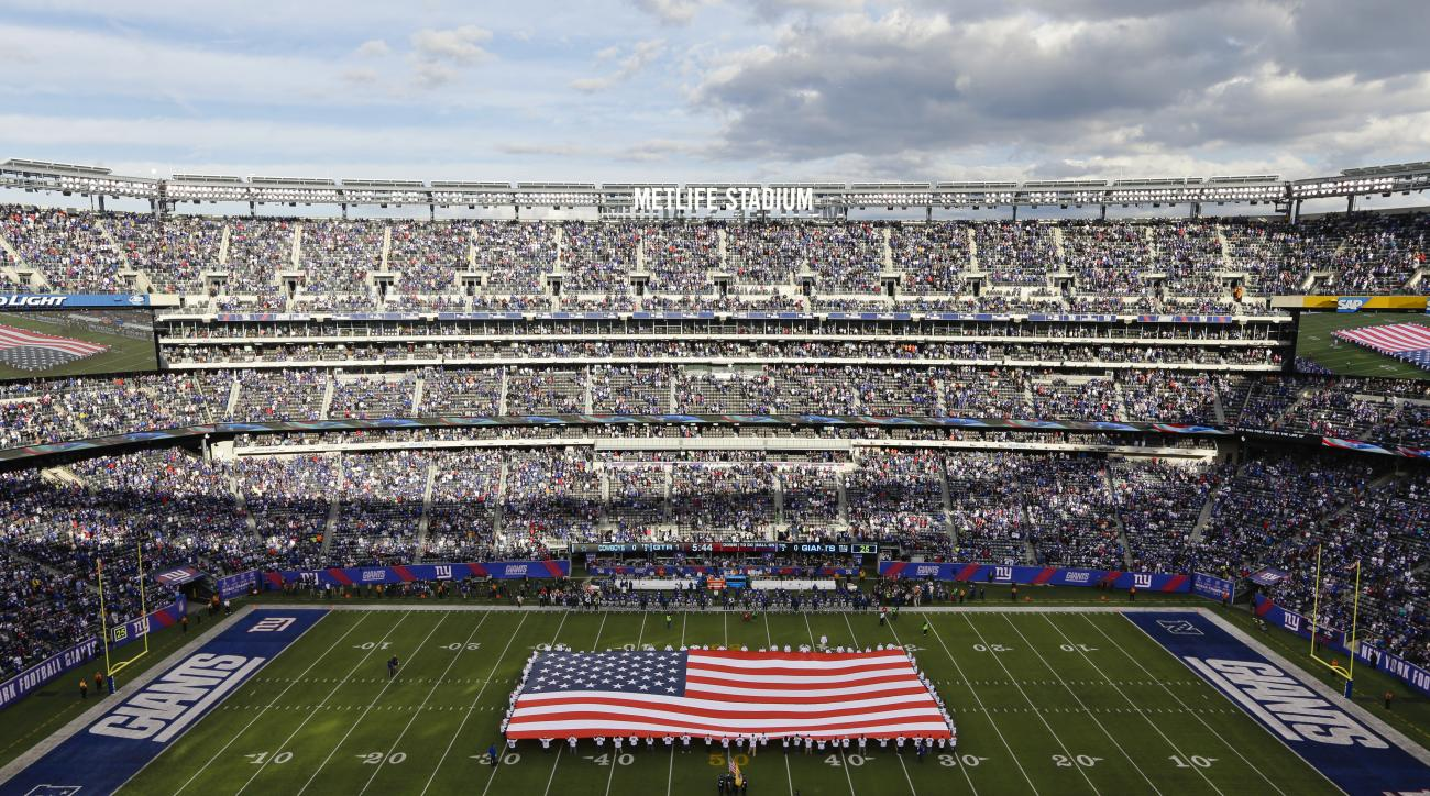 Fans watch during the singing of the national anthem before an NFL football game between the New York Giants and the Dallas Cowboys at MetLife Stadium Sunday, Oct. 25, 2015, in East Rutherford, N.J. (AP Photo/Seth Wenig)