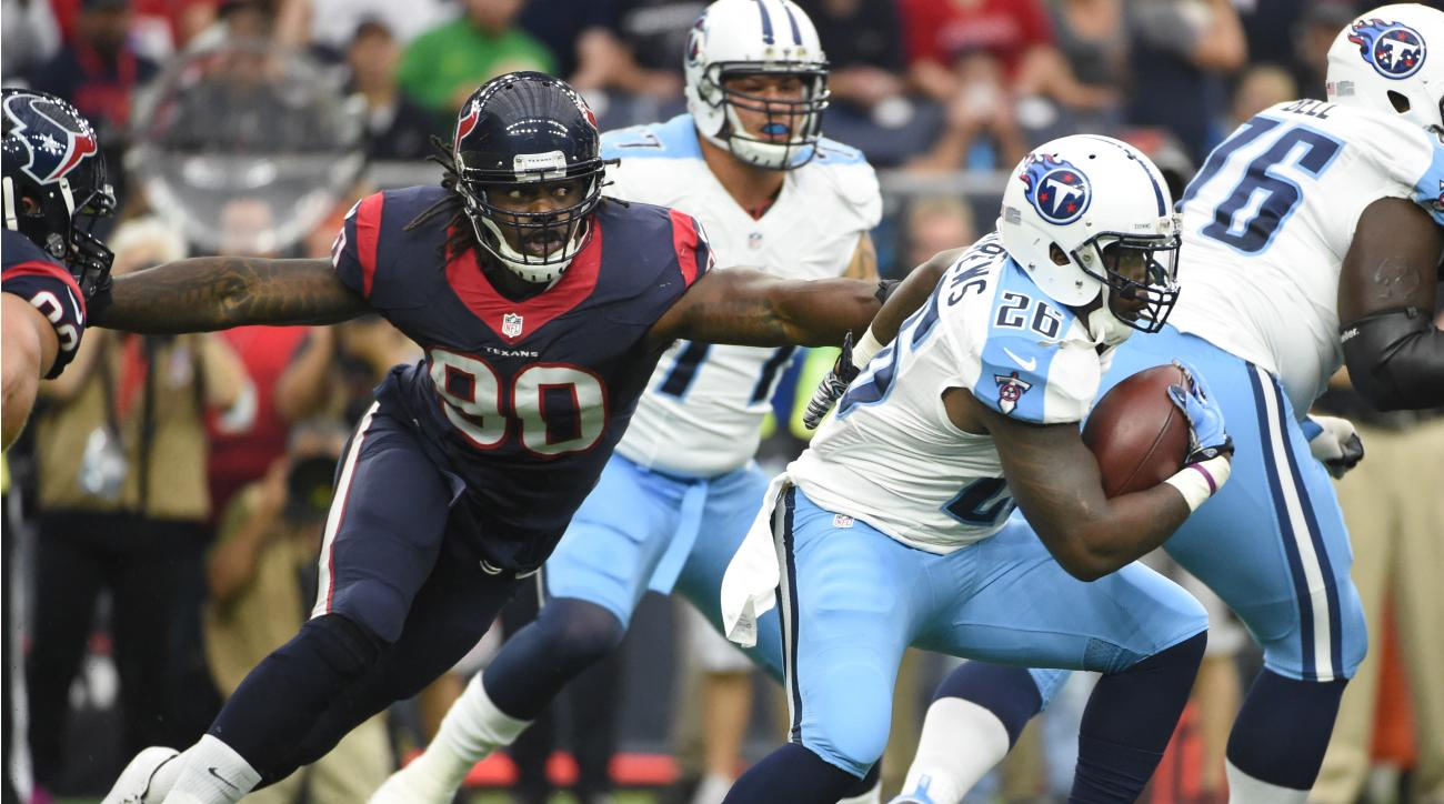 Tennessee Titans running back Antonio Andrews (26) is pursued by Houston Texans outside linebacker Jadeveon Clowney (90) during the first half of an NFL football game, Sunday, Nov. 1, 2015, in Houston. (AP Photo/Eric Christian Smith)