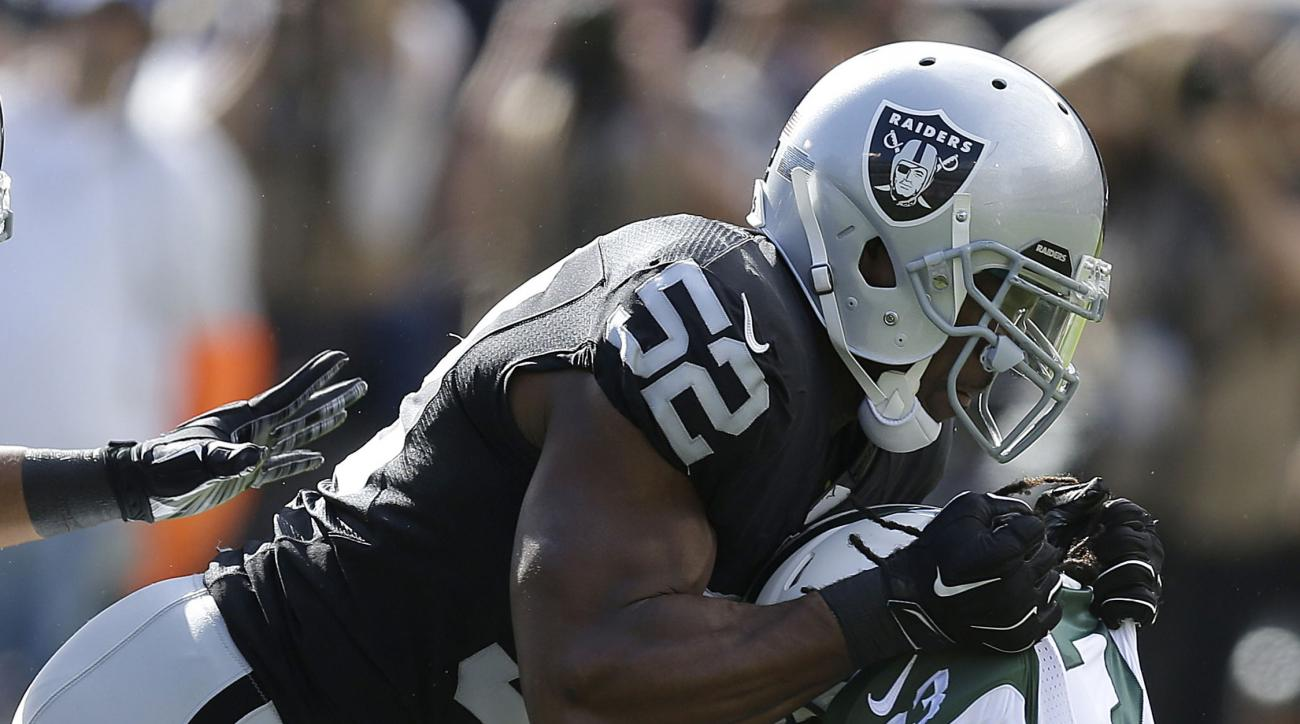 Oakland Raiders outside linebacker Khalil Mack (52) tackles New York Jets running back Chris Ivory during the first half of an NFL football game in Oakland, Calif., Sunday, Nov. 1, 2015. (AP Photo/Ben Margot)