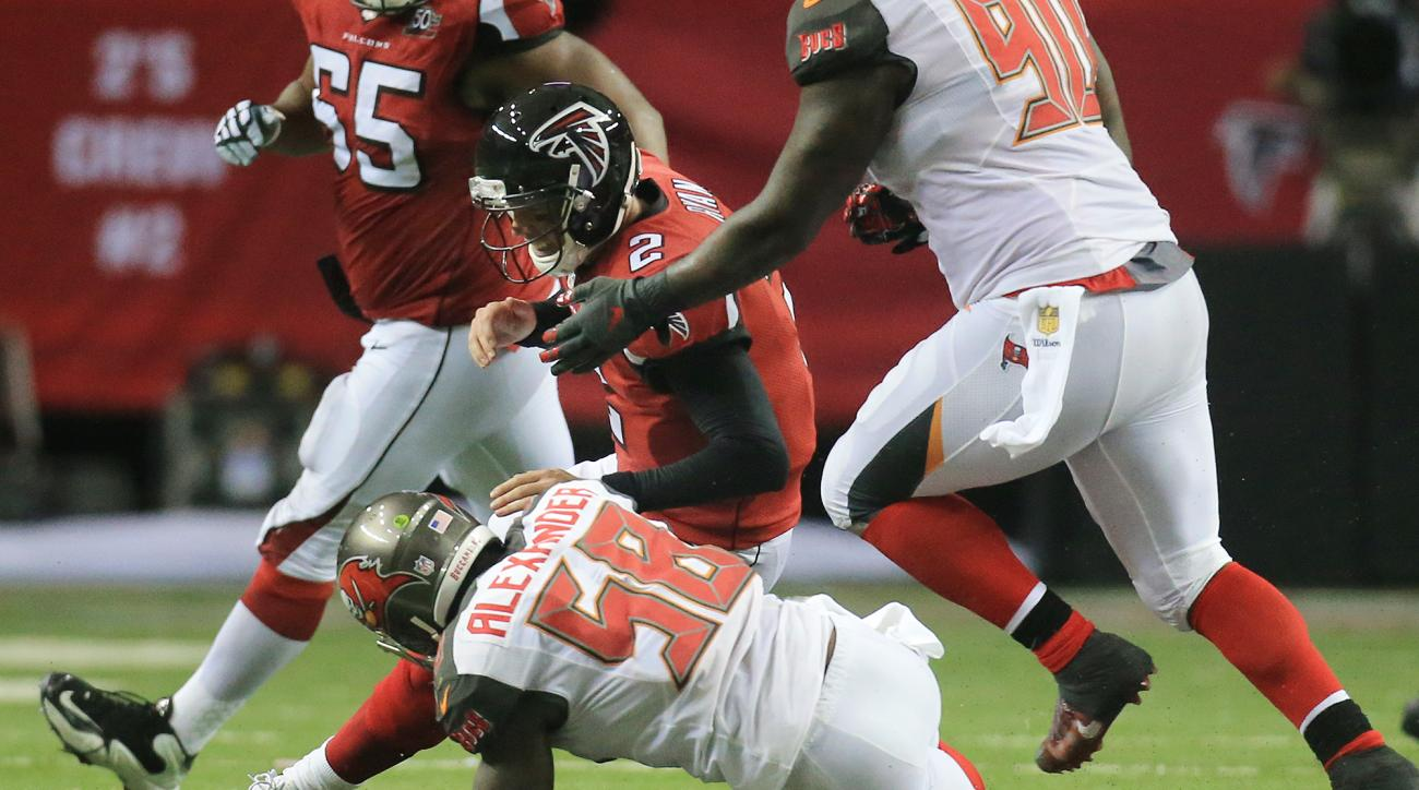 Atlanta Falcons quarterback Matt Ryan helps tackle Buccaneers linebacker Kwon Alexander after Alexander intercepted Ryan during the second quarter in a football game on Sunday, Nov. 1, 2015, in Atlanta. (Curtis Compton/Atlanta-Journal Constitution via AP)