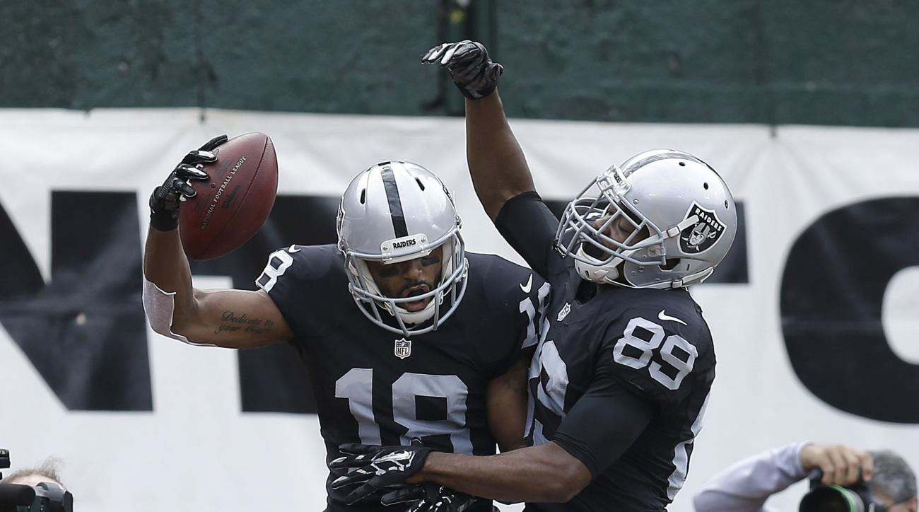 Oakland Raiders wide receiver Andre Holmes (18) celebrates after catching a touchdown pass with wide receiver Amari Cooper (89) during the first half of an NFL football game against the New York Jets in Oakland, Calif., Sunday, Nov. 1, 2015. (AP Photo/Ben