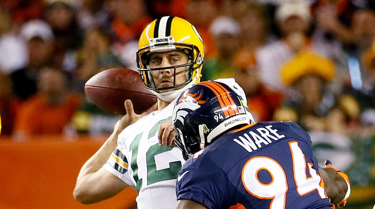 Green Bay Packers quarterback Aaron Rodgers (12) throws under pressure from Denver Broncos outside linebacker DeMarcus Ware (94) during the first half of an NFL football game, Sunday, Nov. 1, 2015, in Denver. (AP Photo/Jack Dempsey)