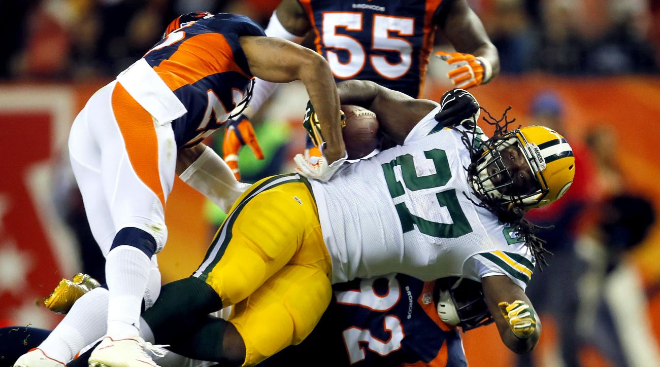 Green Bay Packers running back Eddie Lacy (27) is hit by Denver Broncos nose tackle Sylvester Williams (92) and cornerback Chris Harris (25) during the second half of an NFL football game, Sunday, Nov. 1, 2015, in Denver. (AP Photo/Joe Mahoney)