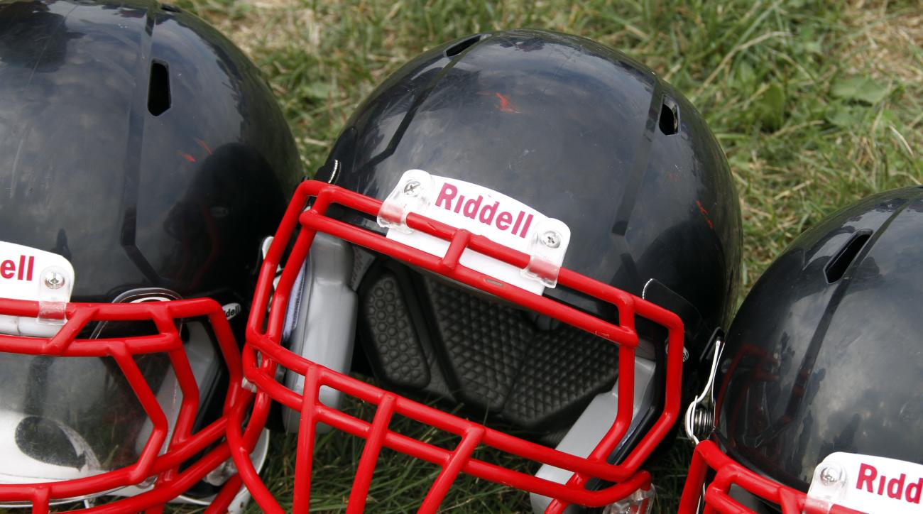 FILE - In this Aug. 4, 2012, file photo, Riddell football helmets that were given to a group of youth football players from the Akron Parents Pee Wee Football League are shown in Akron, Ohio. Seven football organizations are about to receive equipment fro