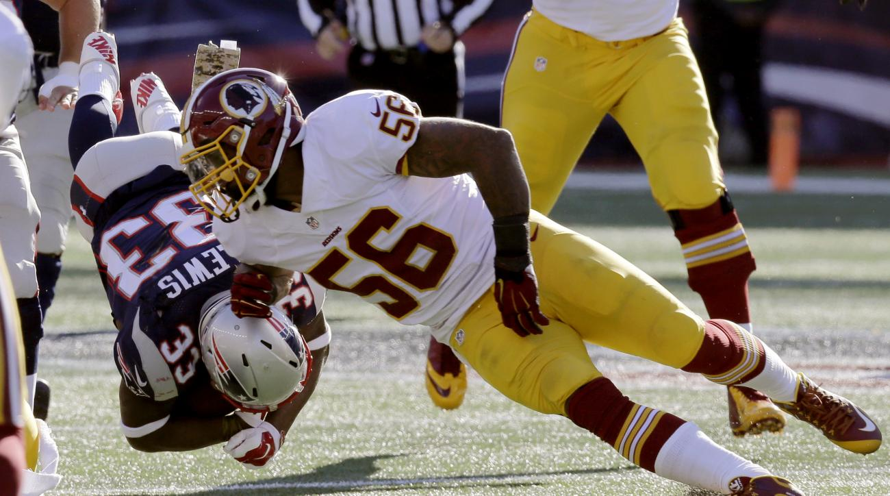 Washington Redskins linebacker Perry Riley (56) knocks down New England Patriots running back Dion Lewis (33) during the first half of an NFL football game, Sunday, Nov. 8, 2015, in Foxborough, Mass. (AP Photo/Charles Krupa)