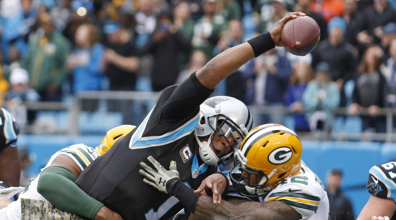 Carolina Panthers' Cam Newton (1) reaches the ball over the goal line for a touchdown against the Green Bay Packers in the first half of an NFL football game in Charlotte, N.C., Sunday, Nov. 8, 2015. (AP Photo/Bob Leverone)