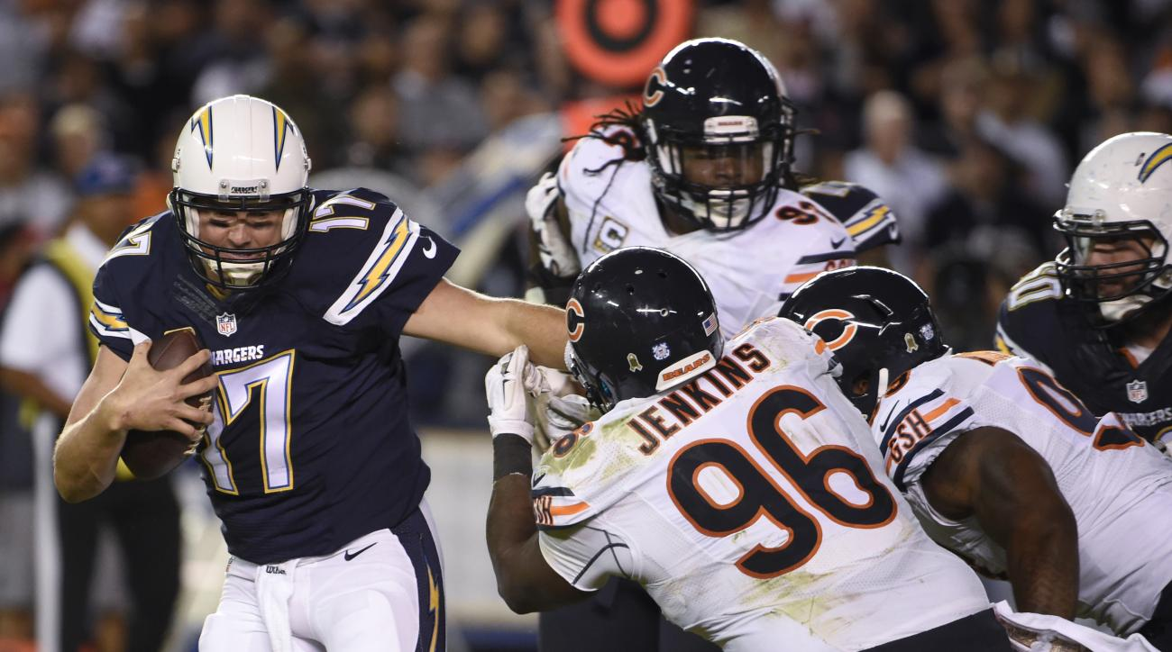 San Diego Chargers quarterback Philip Rivers, left, gets away from Chicago Bears defensive end Jarvis Jenkins (96) and others during the first half of an NFL football game Monday, Nov. 9, 2015, in San Diego. (AP Photo/Denis Poroy)