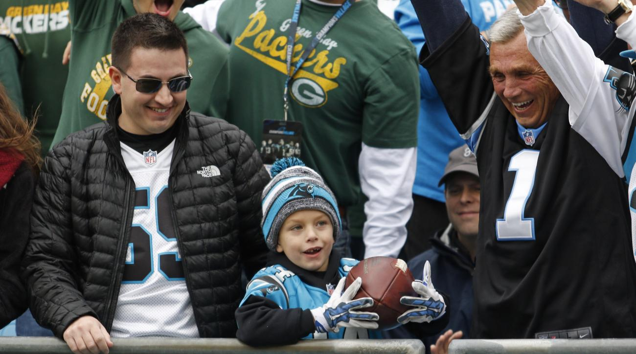In this Sunday, Nov. 8, 2015, photo, Colin Toler, 6, center, holds a football from Carolina Panthers' Cam Newton after Newton's touchdown run against the Green Bay Packers in the first half of an NFL football game in Charlotte, N.C. Toler attended Sunday'