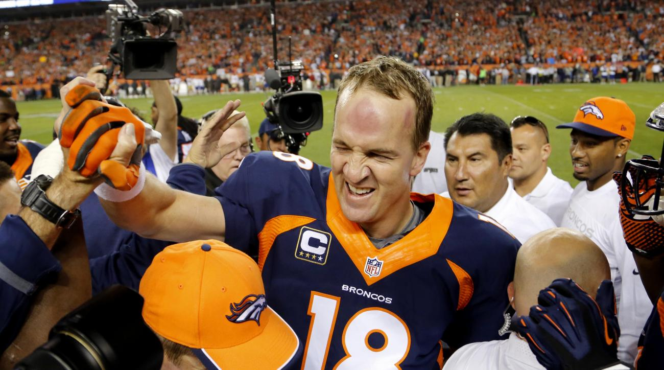 FILE - In this Oct. 19, 2014, file photo, Denver Broncos quarterback Peyton Manning celebrates his 509th career touchdown pass with teammates during the first half of an NFL football game against the San Francisco 49ers in Denver. Manning topped Brett Fav